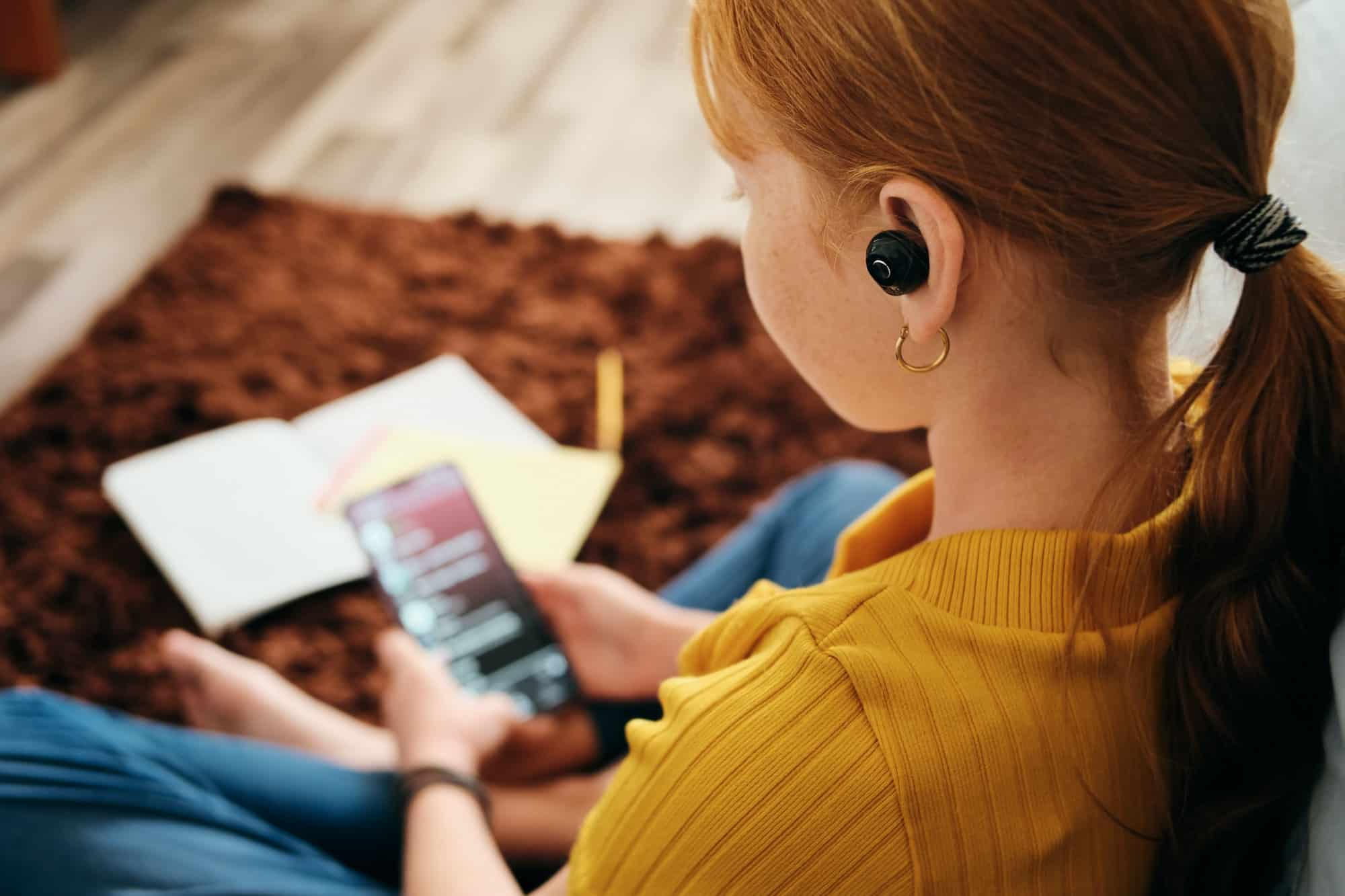 How Do I Turn Up the Bluetooth Volume On My iPhone- Preteen Girl Listening To Music With Wireless Earphones