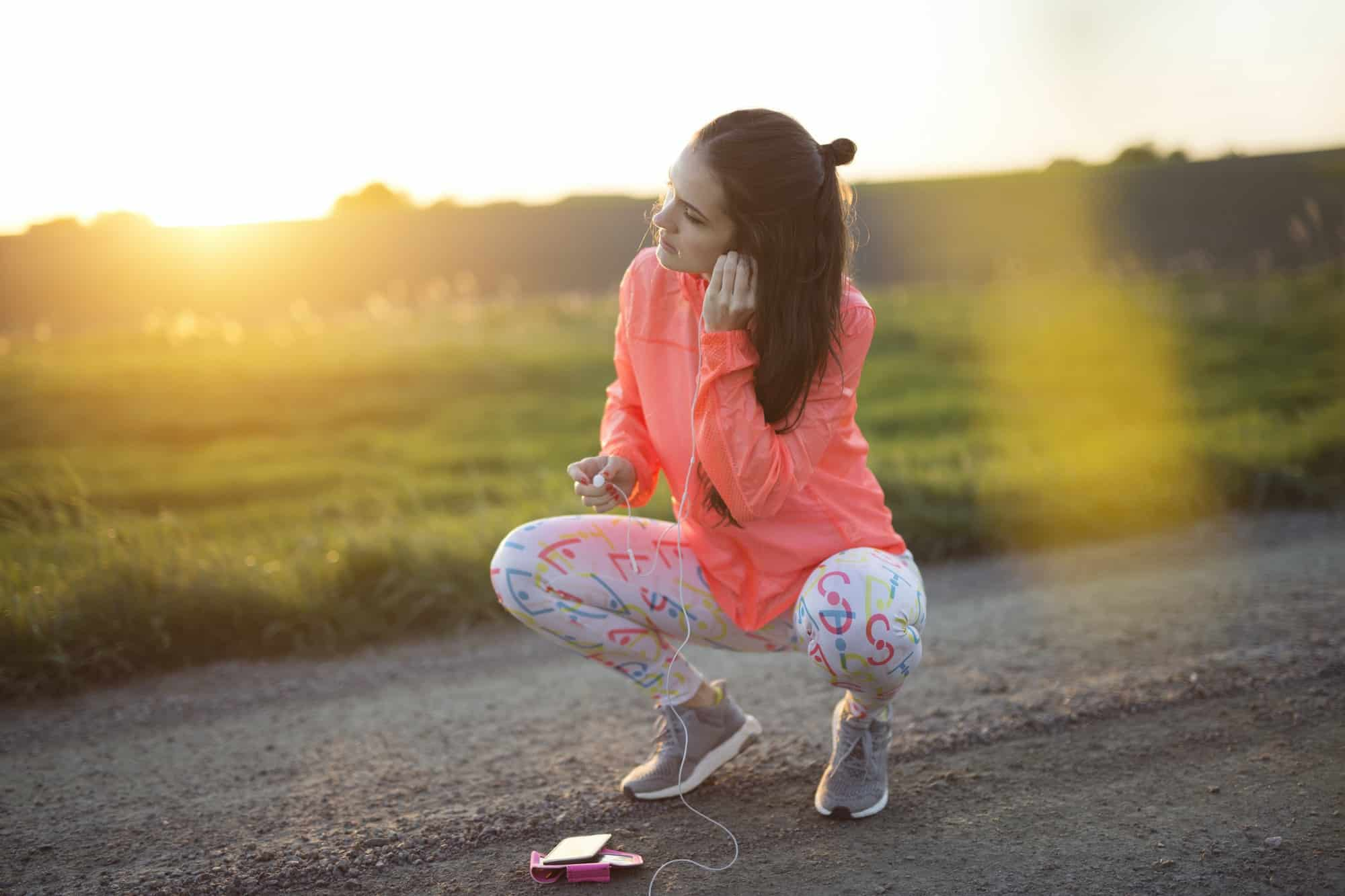 Woman crouching on dirt road and putting headphones in ear
