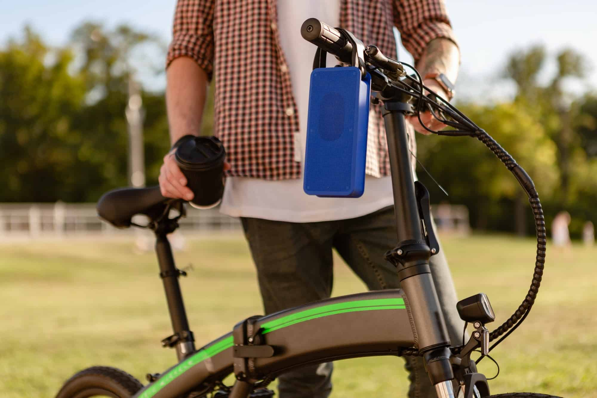 details of hipster stylish man in park listening to music on using electric bicycle