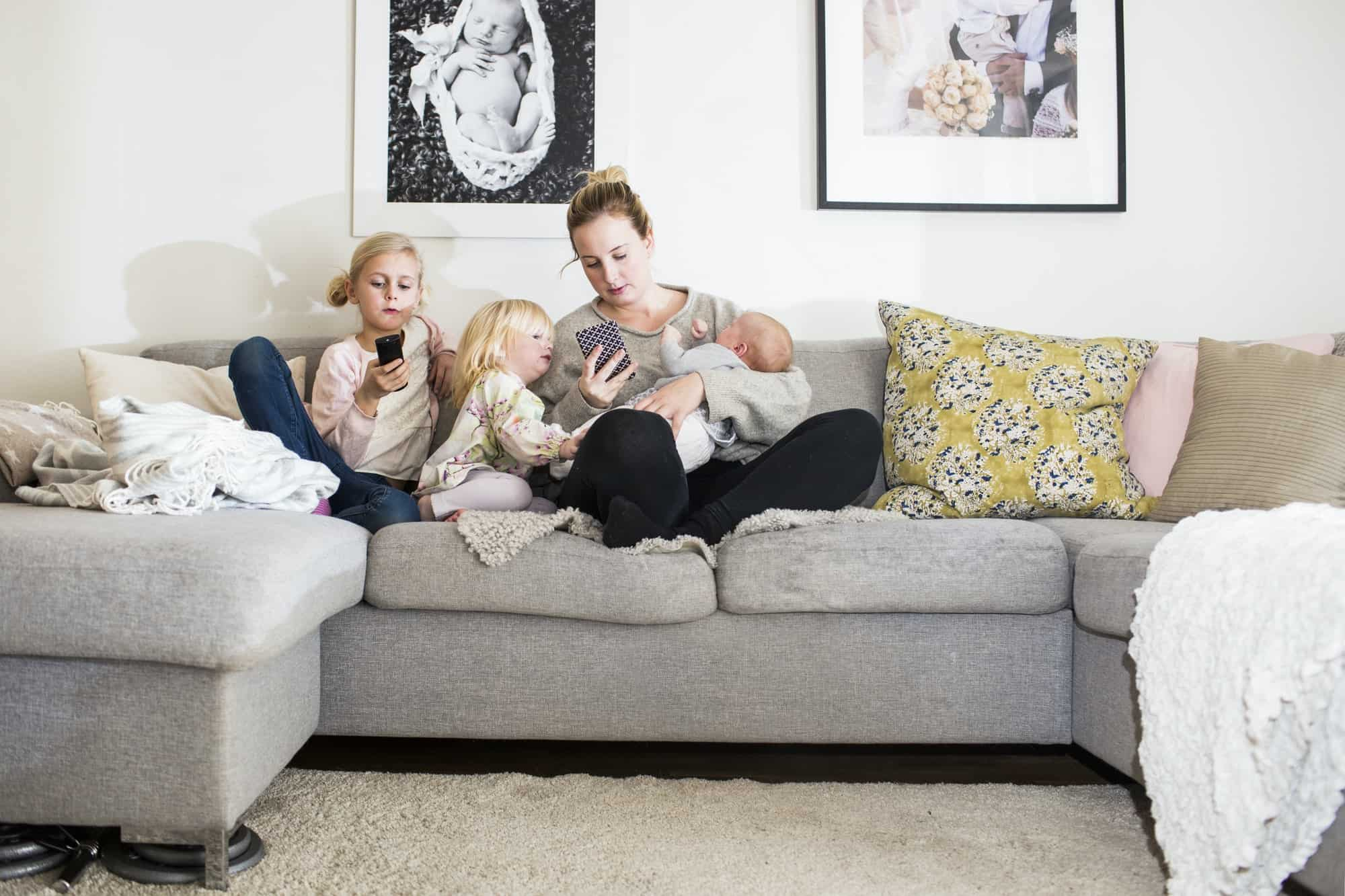 Girls sitting by mother on sofa at home