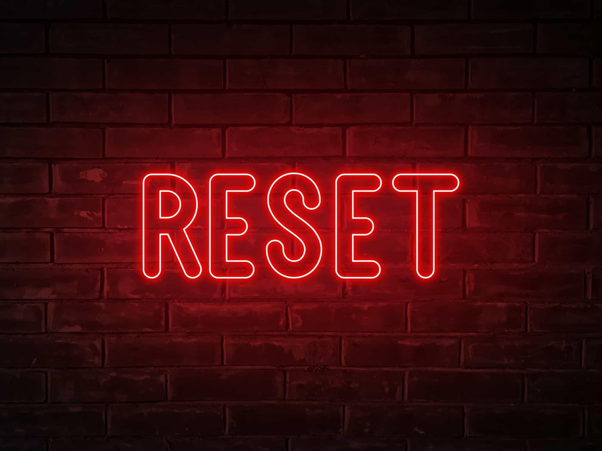 Reset - neon light word on brick wall background